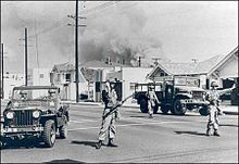 Soldiers of California's 40th Armored Division direct traffic away from an area of South Central Los Angeles burning during the Watts riot, August 11-17, 1965. Whole city blocks were gutted by arson and mob set fires that the fire department was powerless to control due to sniper attacks