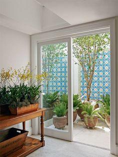O jardim está sempre ali, emoldurado em grandes janelas e portas de vidro nesta casa carioca. O verde participa sem cerimônia de todos os ambientes