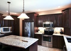 dark kitchen with light countertops. I like this as white cabinets tend to show dirt and finger prints.