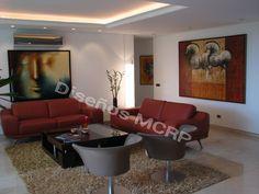 Salón formal, sofás en cuero Italiano, mesa centro de diseño en Wengue, mueble Vitrina Bar de diseño en Wengue.