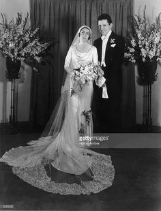 Full-length portrait of American film producer David O. Selznick (1902 - 1965) and his first wife, Irene Mayer, on their wedding day at the home of the bride's parents, Mr. and Mrs. Louis B. Mayer. Mayer wears a white bias-cut gown with a long lace veil while holding a bouquet; Selznick wears white tie and tails.