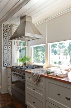 from bliss blog (love the tiles on the wall and the range in front of the window!)