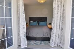 French doors in master bedroom, open to the backyard. Tufted grey headboard with blingy buttons Grey Headboard, Birdhouse, French Doors, Oversized Mirror, Master Bedroom, Backyard, Buttons, Travel, Furniture