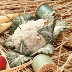 Cauliflower pin cushion made of quilted leaves with the center covered in french knots embroidery. Amazing.