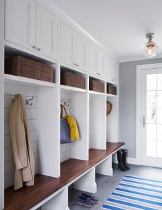 Gray and blue striped mudroom rug layered on concrete gray tiles under a clear glass schoolhouse flush mount light.