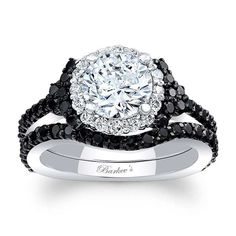 This unique white gold black and white diamond halo engagement set features a prong set round diamond center, encircled with diamonds and embellished with shared prong set black diamonds on the shoulders and running down the dainty shank.  A matching black diamond set wedding band shadows the engagement ring  for a look of sheer elegance.<br /> <br /> Also available in rose, yellow gold, 18k and Platinum.