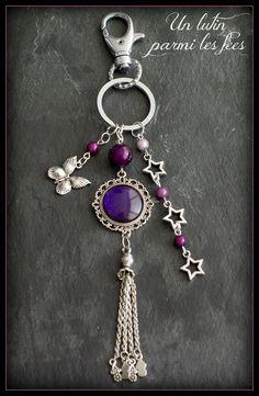 Bijou de sac ou porte clé cabochon couleur violet pailleté, breloque papillon, pompon argenté et étoiles: