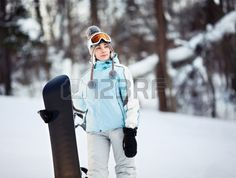 Young female snowboarder standing on ski slope holding her snowboard she is looking away and smiling Stock Photo