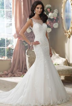 Brides: David Tutera for Mon Cheri. Sleeveless embroidered lace and tulle over memory taffeta soft mermaid wedding dress features an illusion jeweled bateau neckline with scattered hand-beading and edged with delicate beaded trim, drop waist sweetheart lace bodice encrusted with beading and embroidery, plunging open deep V-back illusion bodice with matching scattered beading and trim finished with covered button closures, beaded lace appliqués spill down skirt to scalloped hemline and chapel…