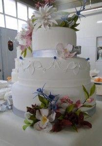 Um bolo de casamento cheio de flores e fitas www.nininhasigrist.com.br
