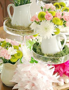 Floral arrangement with cream pitchers sitting in moss on cakestands.
