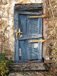 Original comment from Flickr: Une très vieille porte peinte en bleu; les planches sont plus ou moins disjointes; les parties métalliques ont été peintes en jaune. Translation: A very old door painted in blue; the boards are roughly disjointed; metal parts were painted yellow.