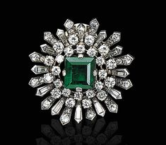AN EMERALD AND DIAMOND CLIP, BY VAN CLEEF & ARPELS   Centering upon a square-cut emerald, within a baguette and circular-cut diamond starburst frame, mounted in platinum, (with attachment to be worn as an ear clip)  Ear clip attachment signed Van Cleef & Arpels, NY, No. 9104