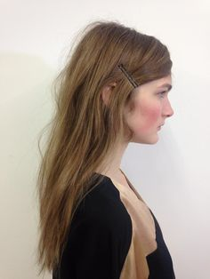 The center-parted, mussed-up texture is accented with bobby pins that keep the hair off the face and add a bit of finesse to the otherwise messy style.