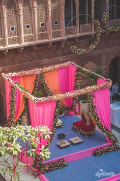 Stunning pink and orange floral mandap decor with drapes #wedmegood #indianwedding #decor #decoration #decorideas #flowers #floral #floralmandap #pink #orange #wedding #mandap #weddingdecoration