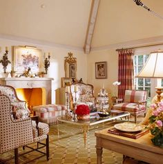 Interior Designer Charles Faudree:  French Flair~~Gilt mirrors flank this living room's fireplace, while two linen-covered French bergéres are pulled close for warmth. Plaids and florals live stylishly together. The living room has French country flair, which is perfect for the Francophile homeowners.