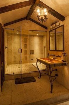 This New Orleans bathroom has stone tile walls and floors, ornate furniture, glass enclosed shower, gabled roof, exposed beam ceilings, and hanging chandelier.