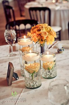 Low centerpiece cluster with floating yellow roses in glass cylinders with clear beads and floating candles and mini bouquet of yellow spray roses, waxflowers, and mini Gerber daisies | Lasting Images Photography | villasiena.cc