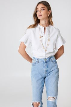 The Flounce Shirt by Debiflue x NA-KD features buttons down the front, flounced sleeves, a soft cotton touch, and a straight fit.