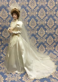 """The Gibson Girl Bride Doll Pure romantic radiance in shim-mering satin, point d'esprit lace and billowing tulle. Wearing her wedding band gleaming with 24 karat gold. And carrying a bridal bouquet Of creamy satin roses.  Approx. 23"""" (58.4 cm) in height.  The Franklin Mint. 1991"""