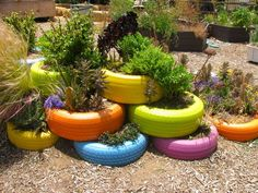painted tires garden - colorful planters would make a great border for driveways, too. Tire Garden, Garden Art, Fence Garden, Garden Deco, Old Tire Planters, Painted Tires, Patio Tiles, Old Tires, Recycled Tires