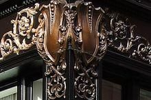 This turn-of-the-century Beaux Arts building features two cast iron stories adorned with gilded shields.