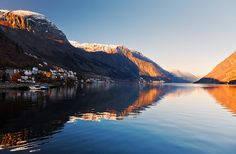 The mountain peaks surrounding Odda glow orange in the evening light. The town enjoys an excellent view located at the end of the Hardangerfjord. Photo: John & Tina Reid