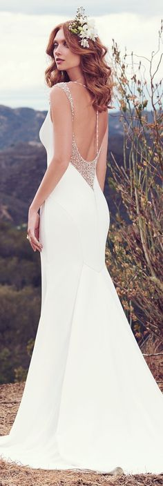 Simple yet chic, this wedding dress by Maggie Sottero features illusion and Swarovski crystals accenting the shoulders, gliding into a shimmering ribbon of pearls and beading that ties in the plunging back, also trimmed in illusion and Swarovski crystals. #weddingdress #weddingdresses #bridalgown #bridal #MaggieSottero