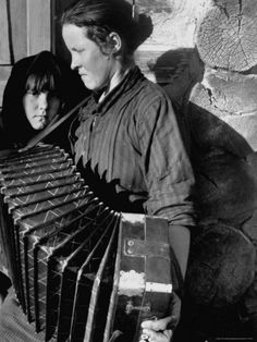 Woman playing a button accordion (баян) as her young girl looks on, Magnitogorsk, 1931 by Margaret Bourke-White I think this is a Concertina. My Grandmother brought one with her in 1900 from Italy Documentary Photographers, Female Photographers, Life Magazine, Ukraine, Button Accordion, Margaret Bourke White, Chant, Black N White Images, World Cultures