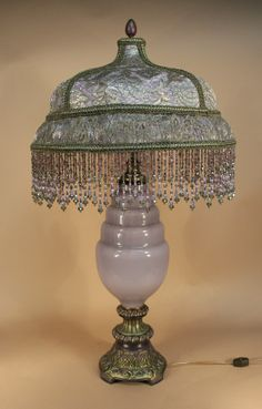 Art Deco table lamp with ornate base and shade covered in violet colored silk and metallic laces