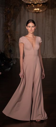 Super Chic. The Cara dress by Jenny Yoo Spring 2019 has a sleek fit & flare silhouette with a modern plunging V neck in our form-fitting Knit Crepe. Cap sleeves create a clean & sophisiticated look, while the flirty deep V in the front & the back of the bodice compliments the dramatic center slit in the long bias cut A Line skirt. Bodice lined. Shown in a gorgeous pink / blush, available in more colors! 'Cara' is a perfect guest of wedding or fall / winter occasion dress!