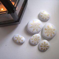 snowflake rocks - paint rocks white and use fine-tip gold metallic pen to draw snowflakes