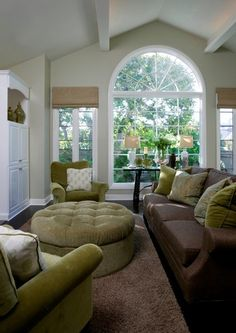 light grey walls, chocolate brown sofa, sage green accent color and large windows