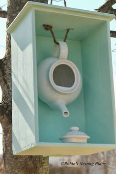 I have teapots I bought to hang as bird houses I like this idea better with an old door from dresserteapot bird house, so cute! could probably get everything you need from garage sales :)