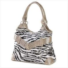 Head-turning looks set this stunning purse ahead of the crowd! A winning combination of wild zebra print, dazzling sequins and faux crocodile trim make this a guaranteed trend setter. Roomy single center compartment. Zipper closure at top.   Weight 1.2 lbs. Fabric, synthetic leather, and sequin...