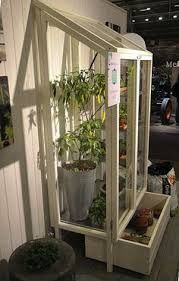 indoor greenhouse Use the wire shelving as a translucent-but-study shelves.Plexiglas for the sides, and a reclaimed caster-ized star freezer for the bottom : A Green Vitrine for Your Balcony Gardenista Large Greenhouse, Greenhouse Shed, Indoor Greenhouse, Greenhouse Gardening, Greenhouse Film, Mary Moon, Balcony Garden, Garden Beds, Glass House