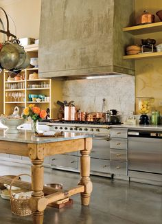 Furniture groupings define the dining and sitting areas of the large room, while the kitchen is clearly designated by the impressive range hood. A food-themed mural on the sink wall introduces a hint of pattern.
