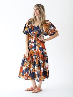 Flowy, midi-length dress with tiered skirt. Color: Marigold Material: 100% cotton Made in the USA. Worn with K Jacques sandals. Model is wearing size 0/XS.