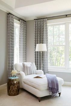 Chic bedroom reading corner is filled with a white roll arm chaise lounge draped in a purple throw blanket and a Horchow Melisande Honeycomb Garden Stool placed in front of windows dressed in black and white patterned curtains.