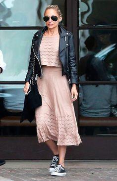 Nicole Richie usa conjunto de saia midi e cropped, jaqueta de couro, tênis all star e óculos aviador.
