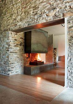 The smooth finish of this sleek, open fireplace contrasts with the heavy, rustic stone walls; Ferran López Rehabilitación Mas de la Riba