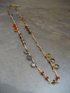 This hand wire wrapped necklace has a stunning collection of faceted genuine gemstones, with plenty of sparkle it is simply a piece that will match any outfit. It is delicate and yet very eye catching with gems such as labradorite, whiskey quartz, spessatine, grey moonstone, smoky quartz and madeira citrine.  Each stone is individually hand wire wrapped with 14k gold filled wire, all chain and the lobster clasp are also 14k goldfilled.  This necklace measures 17 inches in length and has a…