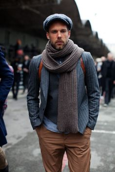 Shop this look for $281:  http://lookastic.com/men/looks/flat-cap-and-scarf-and-backpack-and-chinos-and-denim-shirt-and-blazer-and-waistcoat/521  — Blue Flat Cap  — Grey Woven Scarf  — Brown Leather Backpack  — Tobacco Chinos  — Blue Denim Shirt  — Grey Vertical Striped Blazer  — Charcoal Waistcoat