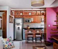 Em tom natural, a madeira promove a união dos espaços, além de trazer aconchego e elegância.  Ripas de madeira compõem as portas dos armários e a paredinha rente à mesa. Na parede da pia, as pastilhas são de porcelana. Projeto de Rosa Brandão e Mila Regina.