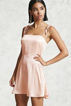 A textured woven dress featuring a square neckline, cami straps with attached self-ties at the shoulders, lining at the front bodice, a concealed back zipper, and A-line silhouette.