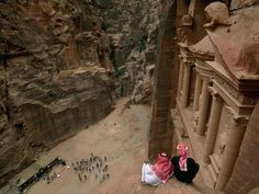 Petra Lookout  Photograph by Annie Griffiths Belt  Lookouts on a ledge, Bedouins watch as a group of tourists admire Al Khazneh (the Treasury), whose function in Nabataean times is still unknown. Spurred by Jordan's peace treaty with Israel, tourism to Petra is up tenfold since 1991, boosting the economy but raising concerns about preservation.