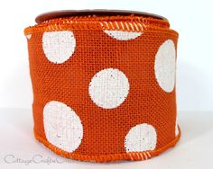 """Bold white polka dots printed on wide 4"""" orange burlap ribbon, 100% natural jute with a wired edge."""