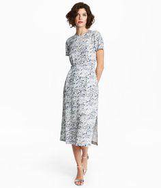 Weiß/Gemustert. PREMIUM QUALITÄT. Langes, figurbetontes Seidenkleid mit Musterdruck. Das Kleid hat kurze Ärmel und einen Schlitz im Rücken. Hinten ein