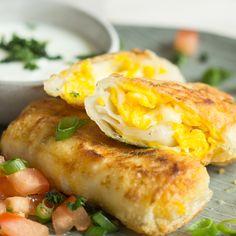 Hier hat sich goldgelbes Rührei mit würzigem Käse in kleinen Teigtäschchen versteckt, die zusammen mit kühler Sour Cream einen leckeren Snack ergeben.