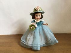 What a find! Madame Alexander Doll - 8 in. She has brunette hair fixed in the perfect little set. On top she wears a little blue straw hat - wide brim adorned with pink flowers and green tulle netting; this ties under her chin with a pink ribbon. | eBay!